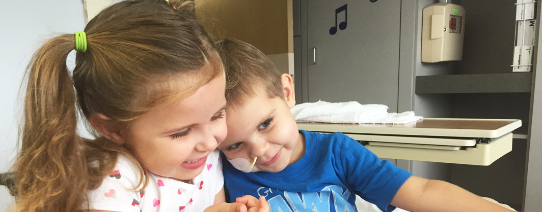 A girl undergoing treatment for cancer snuggles with her older sister