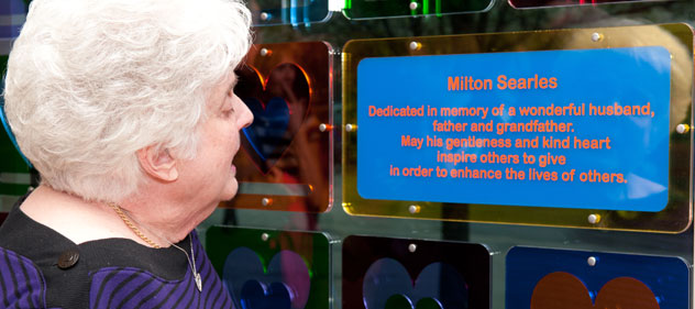 Woman reads description of Milton Searies tribute on the heart wall