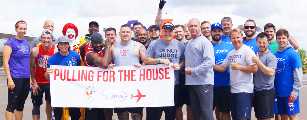 Team of 25 people pose for a picture at the Pull A Plane event