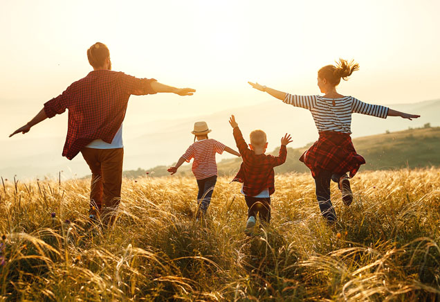 Family running through a field at sunset.